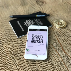 iPhone with Bitcoin wallet and qr code on the screen with bitcoin pen, coin, booklet in background