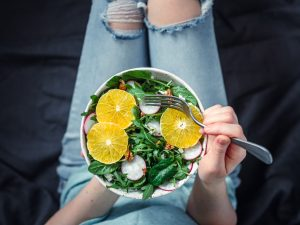 Woman in jeans at bed, holding a plant based salad